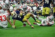 GLENDALE, AZ - JANUARY 01:  Defensive lineman Tyquan Lewis #59 of the Ohio State Buckeyes hits wide receiver Amir Carlisle #3 of the Notre Dame Fighting Irish during the first quarter of the BattleFrog Fiesta Bowl at University of Phoenix Stadium on January 1, 2016 in Glendale, Arizona.  (Photo by Jennifer Stewart/Getty Images)