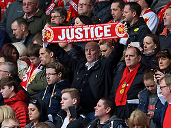 LIVERPOOL, ENGLAND - Friday, April 15, 2016: A Liverpool supporter holds up a Justice scarf during the 27th Anniversary Hillsborough Service at Anfield. (Pic by David Rawcliffe/Propaganda)