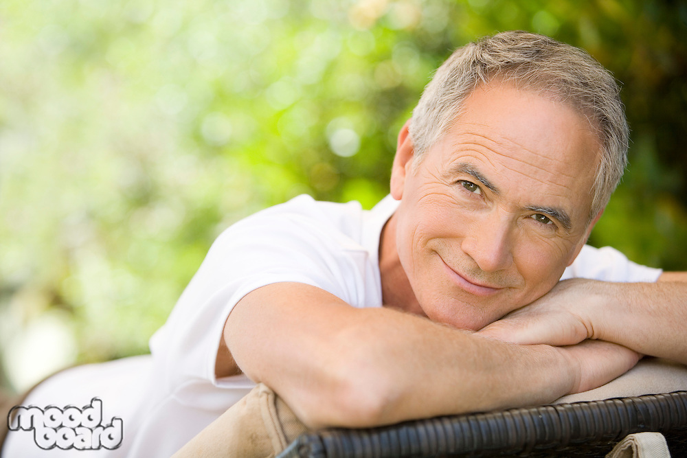 Middle-aged man relaxing on deck chair in garden portrait