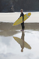 Man carrying surfboard on beach side view