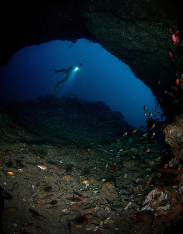 A diver checks out the entrance to a cave. Apo Island is a volcanic island covering 12 hectares in land area, 7 kilometers off the southeastern tip of Negros Island and 30 kilometers south of the Negros Oriental capital of Dumaguete City in the Philippines. Apo Island is one of the world's best known community-organized marine sanctuaries.