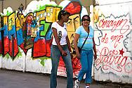 SAÚDE DE CHÁVEZ -  CARACAS - 04/01/2013 .INTERNACIONAL -  Moradoras de Caracas passam por mural de Chávez localizado da Zona Central. Hugo Chávez, que foi operado em Cuba em dezembro último em decorrência de um câncer e tem enfrentado um pós-operatório difícil.  FOTO: DANIEL GUIMARÃES/FRAME
