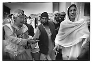 A crowd of mosque beggars put the heat on wealthy Kabuli woman as she leaves the women's section of Shah Doh-Shamshira Mosque, Kabul, Afghanistan.