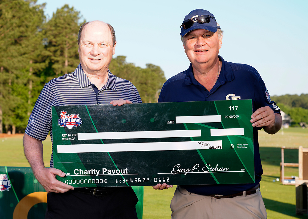 Peach Bowl, Inc. CEO & President Gary Stokan presents Former Georgia Tech head football coach Paul Johnson a check for his charity after the Chick-fil-A Peach Bowl Challenge at the Ritz Carlton Reynolds, Lake Oconee, on Tuesday, April 30, 2019, in Greensboro, GA. (Paul Abell via Abell Images for Chick-fil-A Peach Bowl Challenge)