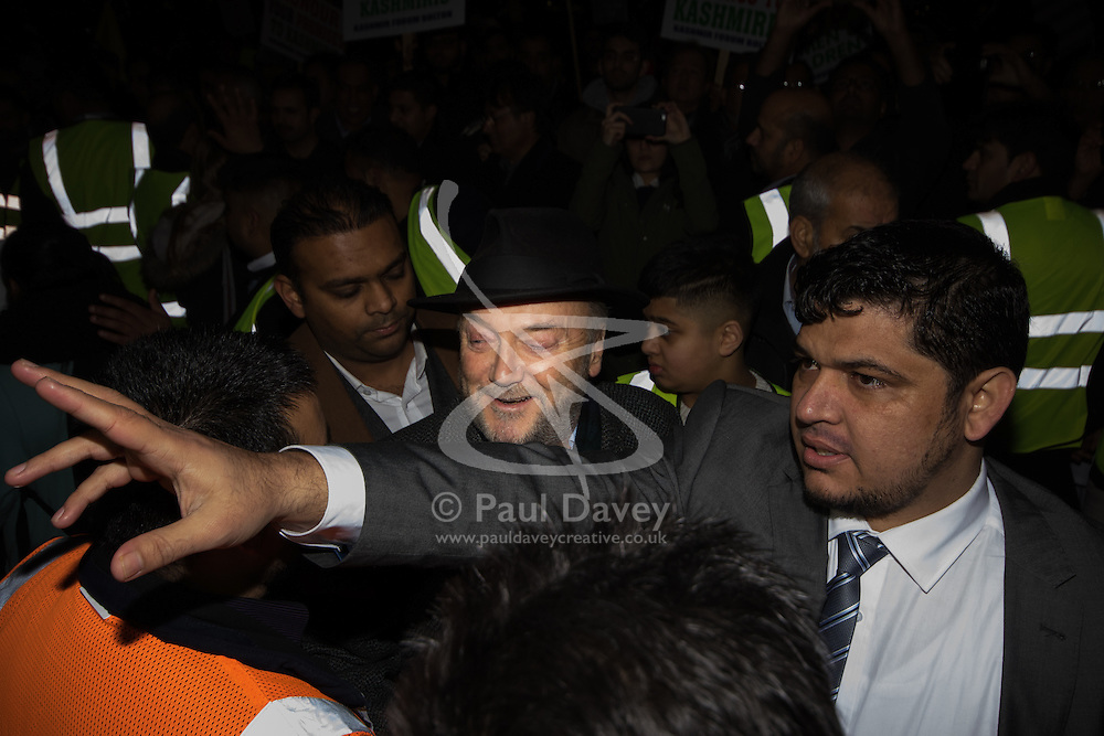 """Amid high security measures, hundreds of Kashmiri protesters, supported by George Galloway, demonstrate outside Wembley Stadium ahead of an address to more than 60,000 Indian expats by Prime Minister Narendra Modi at a 'UK Welcomes Modi' reception. Modi, a Hindu and his BJP party are accused of a wide range of human rights abuses against religious and ethnic minorities in India. PICTURED: George galloway makes his way through the boisterous crowd before delivering a speach criticising Cameron for allowing """"dictator"""" Modi to come to London.6875."""