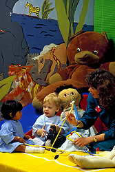 Stock photo of a woman playing with two toddler patients in the children's ward of the hospital