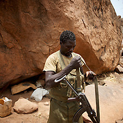 A Sudan People's Liberation Movement (SPLA-N) rebel fighter prepares his weapons for an attack on Sudan's Armed Forces (SAF) positions near Tess village in the rebel-held territory of the Nuba Mountains in South Kordofan.