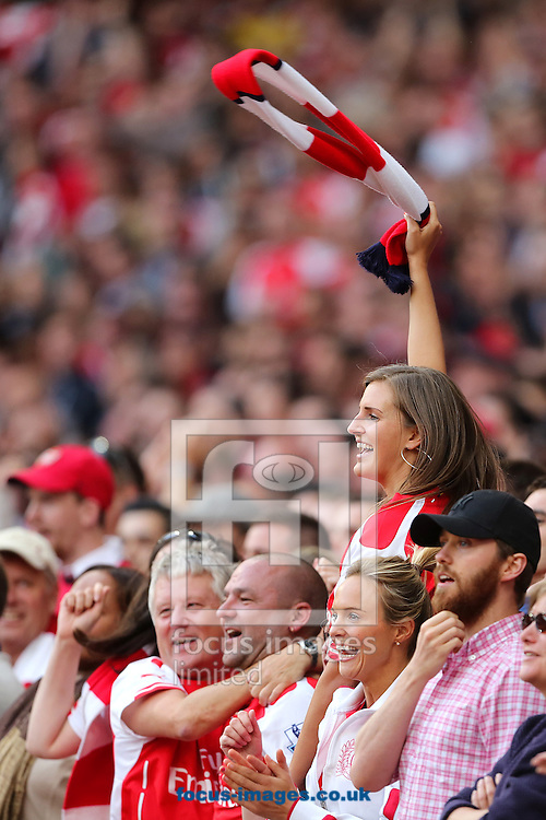 Arsenal fans celebrate after Aaron Ramsey scored the winning goal in a 2-1 win over Crystal Palace in the Barclays Premier League match at the Emirates Stadium, London<br /> Picture by Richard Calver/Focus Images Ltd +447792 981244<br /> 16/08/2014