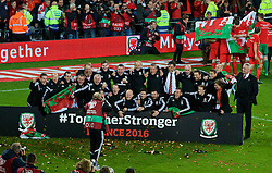 CARDIFF, WALES - Tuesday, October 13, 2015: Wales staff celebrate after qualifying for the finals following a 2-0 victory over Andorra during the UEFA Euro 2016 qualifying Group B match at the Cardiff City Stadium. Masseur David Rowe, Paul Harris, masseur Chris Senior, Kevin McCusker, Mike Murphy, physiotherapist David Weeks, Mark Evans, James Turner, Medical Officer Doctor Jon Houghton, assistant manager Osian Roberts, physiotherapist Sean Connelly, coach Paul Trollope, Doctor Rhodri Martin, goalkeeping coach Martyn Margetson, equipment manager David Griffiths, manager Chris Coleman, Ronan Kavanagh, sport psychologist Ian Mitchall, performance analyst Esther Laugharne, head of fitness and science Ryland Morgans, team operations manager Amanda Smith, sports science coach Adam Owen, chef Michael Knight, coach Kit Symons. (Pic by Paul Currie/Propaganda)