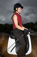 Female horseback rider sitting on brown horse