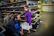 "Julia Bacher and Clifford Lubilz help their daughter Jailyn Lubilz, 7, try on shoes at the Goodwill store in Burlington, Vermont on April 20, 2013.  A young family on a budget, they're conscious of where their money goes. ""She just burns through shoes,"" Clifford said. ""Every so often we do a complete overhaul. This is a good place to do it.""<br />