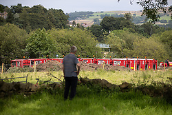 © Licensed to London News Pictures. 04/08/2019. Whaley Bridge, UK. A man looks across past ten pumps that are pulling water out from the reservoir and over undamaged portion of the slipway . Watermarks on the rocks show the amount of water that has been pumped away since yesterday (Saturday 3rd August) . More rain is forecast today (Sunday 4th August) in the town of Whaley Bridge in Derbyshire after earlier heavy rain caused damage to the Toddbrook Reservoir , threatening homes and businesses with flooding. Photo credit: Joel Goodman/LNP