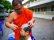 """03 APRIL 2018 - CHIANG MAI, THAILAND: A Buddhist monk shaves a Shan boy's hair before the Poy Sang Long ceremony at Wat Pa Pao in Chiang Mai. Poy Sang Long (""""The Festival of the Crystal Sons"""") is a ceremony that marks a rite of passage among the Buddhist Shan people in Myanmar and northern Thailand. Boys between seven and fourteen years of age are ordained as Buddhist novices during a three day ceremony. Before the ceremony starts the boys have their heads shaved.       PHOTO BY JACK KURTZ"""