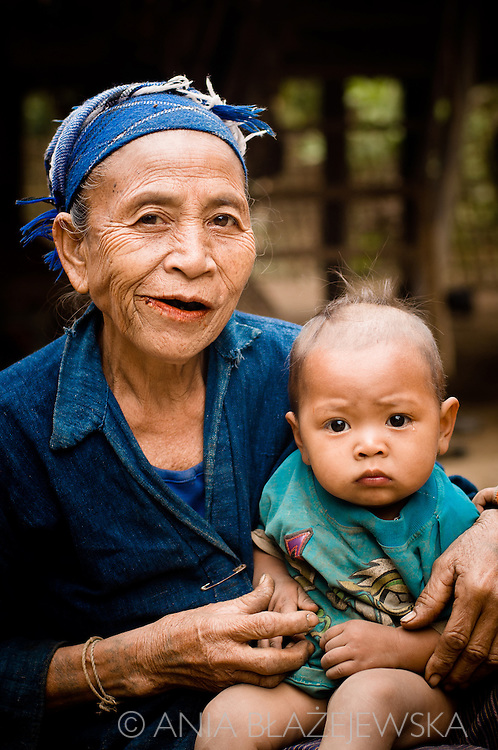 Laos, Luang Nam tha. The Khamu woman with a baby. <br /> <br /> The Khamu arrived in northern Laos and Thailand in the early first millennium AD, making them one of the earliest inhabitants in the region. When the Lao arrived in the area they pushed the Khamu out of the valleys into higher land. <br /> <br /> Traditional Khamu villages can be found in low mountainous areas and forest valleys. The houses are built on low wooden stilts about 1 to 1.5 meters above the ground. The walls are made of bamboo mats without windows, the roof is covered with thatch. Traditional Khamu villages have a communal house, where young adolescent boys live and where men gather for important discussions or to work together on crafts. <br /> <br /> They cultivate rice, maize, cassava, gourds, eggplants, peanuts and vegetables. Besides that Khamu grow tobacco and brew whisky for self-consumption. They keep a few buffaloes, cattle and goats. Pigs and poultry are kept in larger numbers. <br /> <br /> The Khamu believe in several spirits and every village has a guardian spirit. Spirit gates are erected over the entrance to Khamu villages and special houses are built to make sacrifices. The Khamu practice a form of ancestor worship. Every village has a shaman and several sorcerers. <br /> <br /> The Khamu have never engaged intensively in weaving and buy most of their cloths from others. <br /> The festive dress of a Khamu woman includes a long-sleeved dark vest open at the front, often with red hems, a dark based sarong with many colored strings or motifs and a kerchief. On ordinary days Khamu women wear the Lao-styled sarongs and ordinary blouses with a multitude of bright colors. The older women wear a headscarf, the younger women wear their hair bound up in a bun and leave it uncovered. they decorate themselves with silver and copper bracelets can be found on the arms and legs.