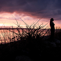 A woman standing against a dark stormy sunset.