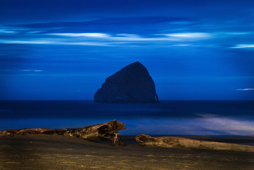 Twilight envelopes the 327 ft. tall Haystack Rock in Pacific City, Oregon. Seen from the patio of The Pelican Pub. The Oregon Coast, a classic, beautiful road trip. Heading West from Portland to Tillamook, with a detour to the fishing village of Garibaldi, through Cape Lookout State Park and on to our final destination of Pacific City.