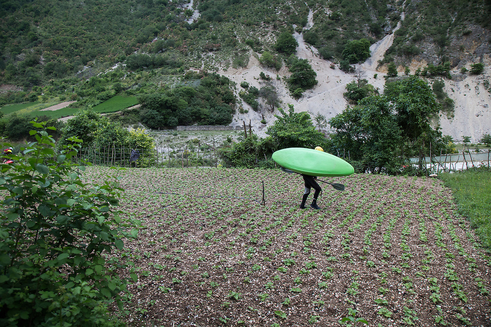 A kayaker participating in the Balkans River Tour, an effort by European river kayakers to raise awareness about the ecological threat posed by dams and hydropower projects to free flowing rivers in the Balkans, walks down a path through a field on the Bancha River, a small tributary of the Vjosa that could be diverted by a hydropower project.