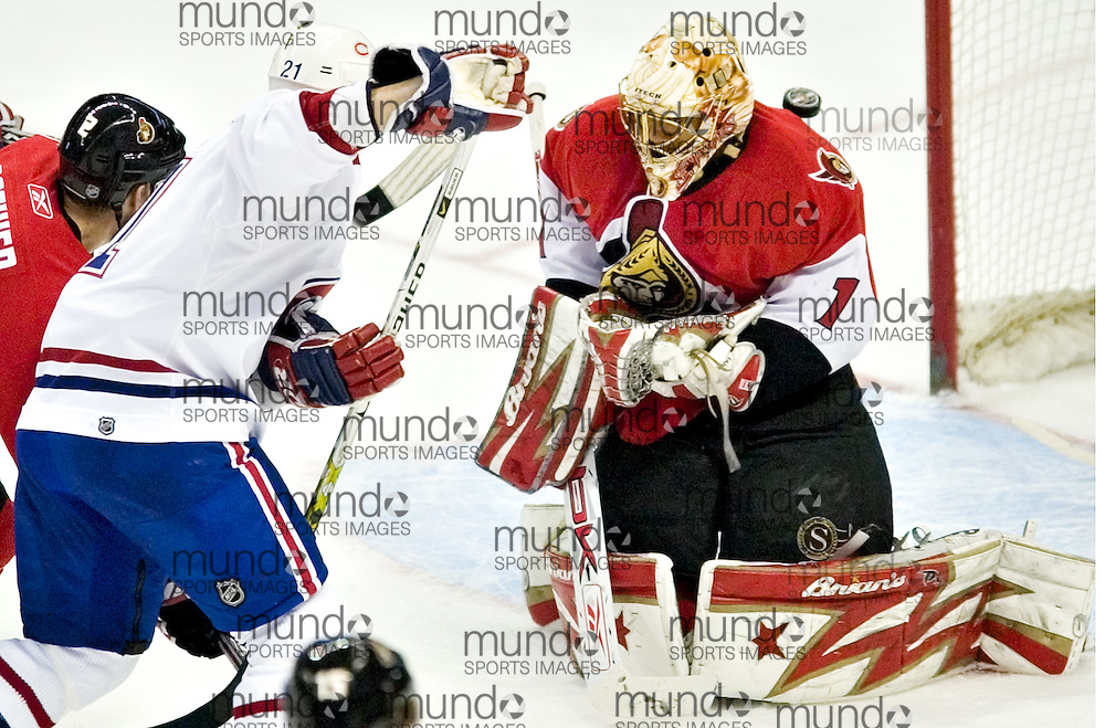 Ottawa Senators goaltender Ray Emery(R) has the puck drop behind him as Montreal Canadiens forward Christopher Higgins crashes the net during NHL action in Ottawa April 6, 2006..REUTERS/Geoff Robins<br />