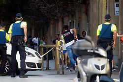 People are escorted by Spanish policemen outside a cordoned off area after a van ploughed into the crowd, killing 13 persons and injuring over 80 on the Rambla in Barcelona, Spain on August 17, 2017. A driver deliberately rammed a van into a crowd on Barcelona's most popular street on August 17, 2017 killing at least 13 people before fleeing to a nearby bar. Officers in Spain's second-largest city said the ramming on Las Ramblas was a 'terrorist attack'.  (Photo by Hugo Fernández Alcaraz/NurPhoto/Sipa USA)