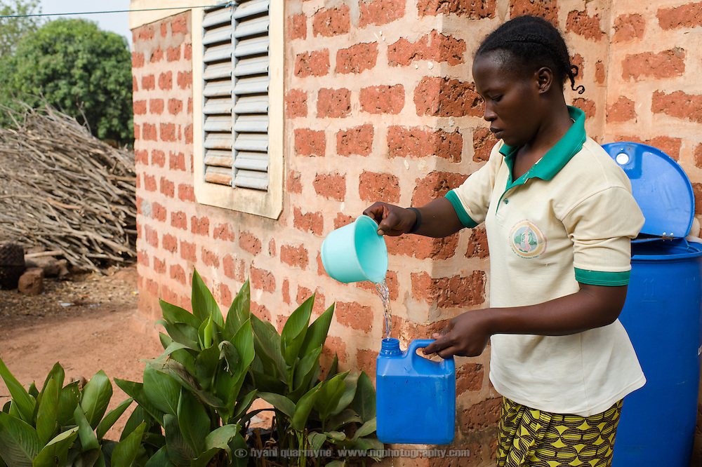 A woman rinsing out a container at the Barro extended family homestead in the village of Toussiana in the Hauts-Bassins region of Burkina Faso, on 22 February 2016.