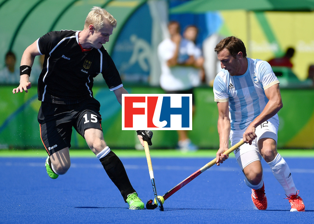 Germany's Tom Grambusch (L) vies with Argentina's Lucas Vila during the men's semifinal field hockey Argentina vs Germany match of the Rio 2016 Olympics Games at the Olympic Hockey Centre in Rio de Janeiro on August 16, 2016. / AFP / Pascal GUYOT        (Photo credit should read PASCAL GUYOT/AFP/Getty Images)