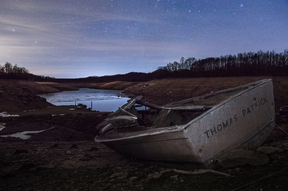 Under a starry night sky, an old abandoned boat is left on the shore of Summersville Lake, drained for the winter.  Shot in West Virginia.