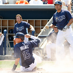 March 20, 2011; Port Charlotte, FL, USA; Tampa Bay Rays shortstop Reid Brignac (15) slides home safe during a spring training exhibition game against the Baltimore Orioles at Charlotte Sports Park.   Mandatory Credit: Derick E. Hingle