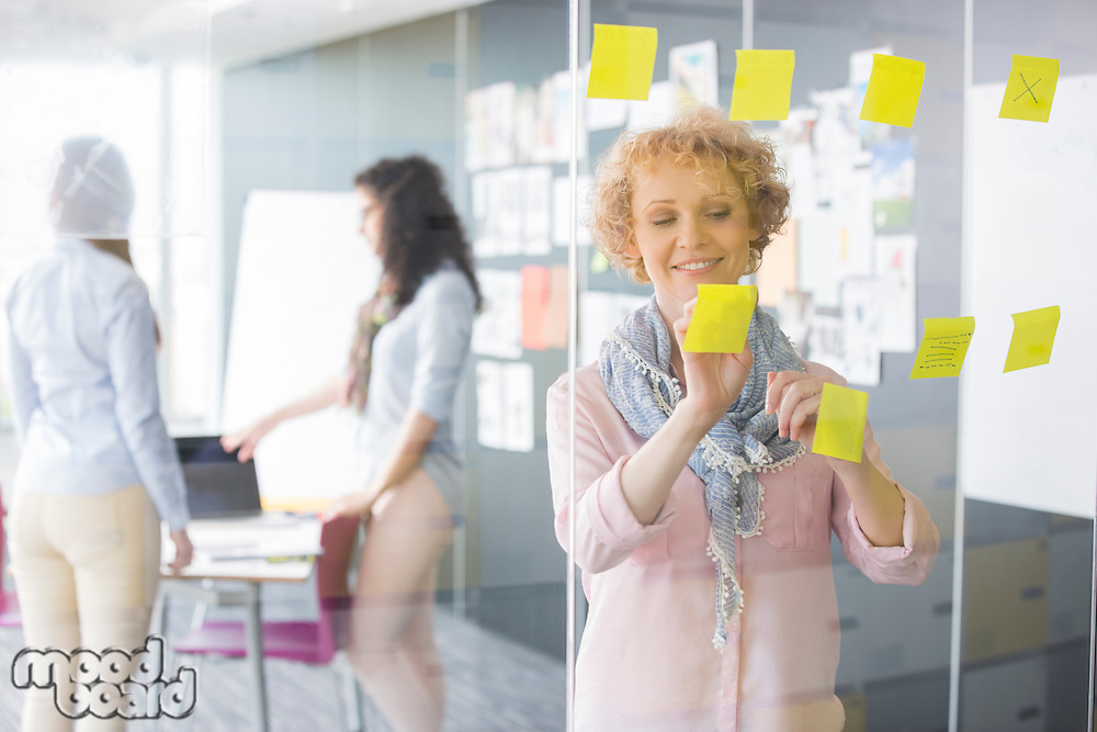 Businesswoman reading sticky notes on glass with colleagues in background