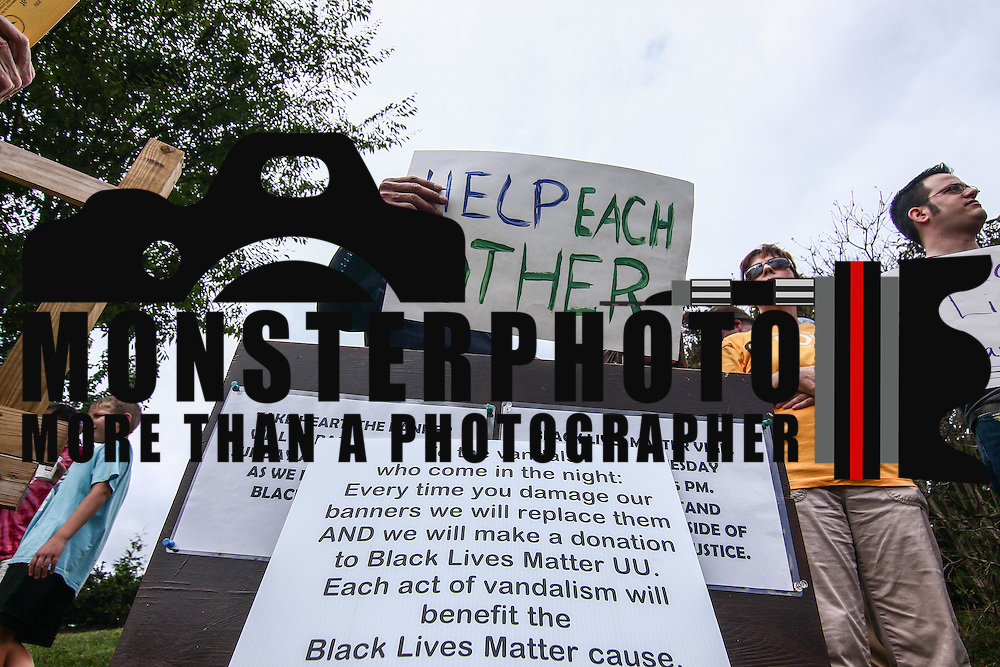 "Retired elected official Theodore ""Ted"" Blunt holds a sign that reads ""Help Each Other"" during a rededication ceremony Sunday, August 21, 2016, at First Unitarian Church in Wilmington."