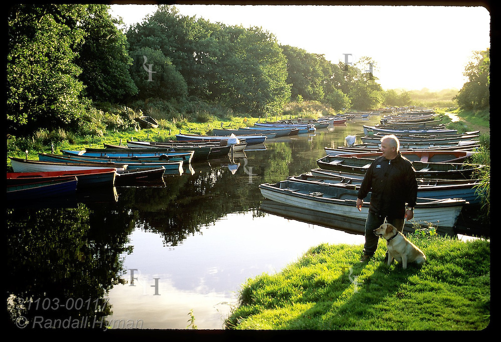 Patrick Hegarty and his golden retriever pause near row of private boats docked in slough off Ross Bay; Killarney Natl Park, Ireland.