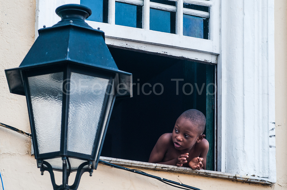 A little bahian boy at the window of a colonial house in the Pelourinho