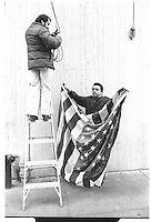Man folding or unfolding American flag, Midtown, New York City. Street photography. 1980