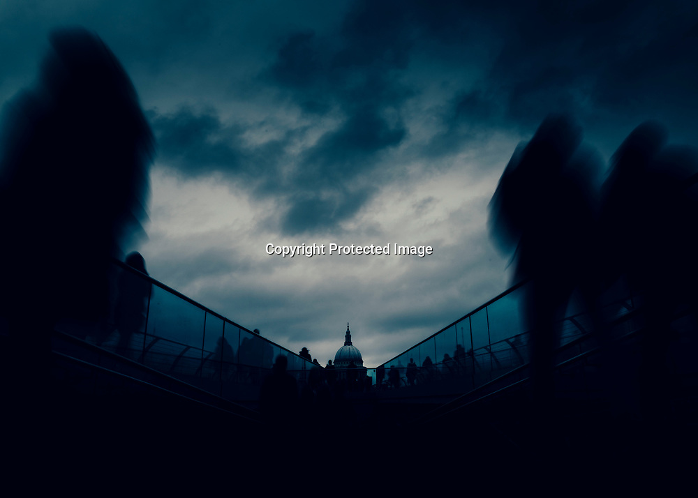 Long exposure of pedestrians at London, England, UK Millenium Bridge with St. Paul's Cathedral in background - dystopia dark post-apocalyptic fine art concept
