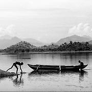 "Sri Lanka.<br /> Two men and a boat at Giritale irrigation tank.<br /> Copyright: Dominic Sansoni<br /> 28"" x 28"""