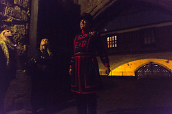 © Licensed to London News Pictures. 23/10/2013. London, UK. The Yeoman warder, Kevin Paul Kitcher, begins outside Traitors' Gate at the start of a twilight tour at the Tower of London which gives visitors a unique after hours view of the UK's most visited historic attraction. The first Twilight Tour at the Tower of London will take place on 3 November 2013 and they will then take place every Wednesday during November, then January, February and March in 2014.Photo credit : Vickie Flores/LNP