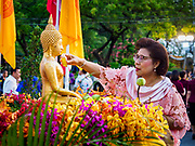 13 APRIL 2018 - BANGKOK, THAILAND:  A woman pours water on a Buddha statue to make merit during the first day of Songkran in Lumpini Park in Bangkok. Songkran is the traditional Thai New Year celebration best known for water fights.   PHOTO BY JACK KURTZ
