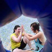 Participants inside a Zorb Globe preparing for  a ride down the hill. The sport of Zorb globe riding was invented in New Zealand and globes are designed, manufactured and tested there, The Zorb globe is an 11 foot high inflatable transparent sphere which you can ride inside. Two feet of air protect you from the ground enabling you to globe ride down hills at high.  Agrodome, Western Rd. Ngongotahaha.  Rotorua, New Zealand,, 11th December 2010 Photo Tim Clayton.