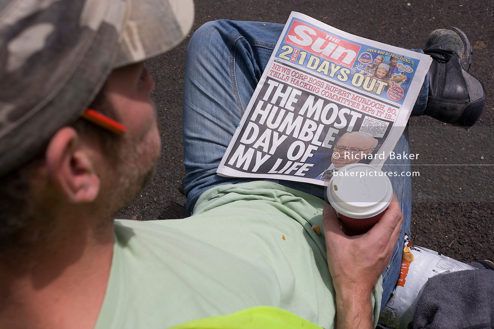 A labourer reads a copy of Britain's tabloid Sun Newspaper. The worker holds a coffee and wears a working mans' cap with a pencil in his right ear as he sits in sunshine during a lunch break. In the context of the News International media scandals of 2011, the (daily) Sun is a sister paper to the now defunct (Sunday) News of The World, closed down by proprietor Rupert Murdoch in the light of public outrage over phone hacking. The Sun's own headline refers to the previous day when Murdoch sat before a Parliamentary Select Committee to answer questions about the nature of phone hacking into private voicemails of victims and their grieving families. Murdoch's overall message was the committee grilling was his most humble day.