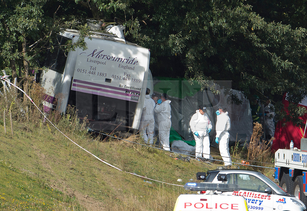 © London News Pictures. 11/09/2012. Hindhead, UK . Forensics entering the bus at the scene of a fatal bus crash on the north bound A3 motorway near Hindhead Tunnel, Hindhead, Surrey on September 11, 2012.Three people were killed and a number of others seriously injured when a coach carrying overturned after crashing into a tree. Photo credit: Ben Cawthra/LNP