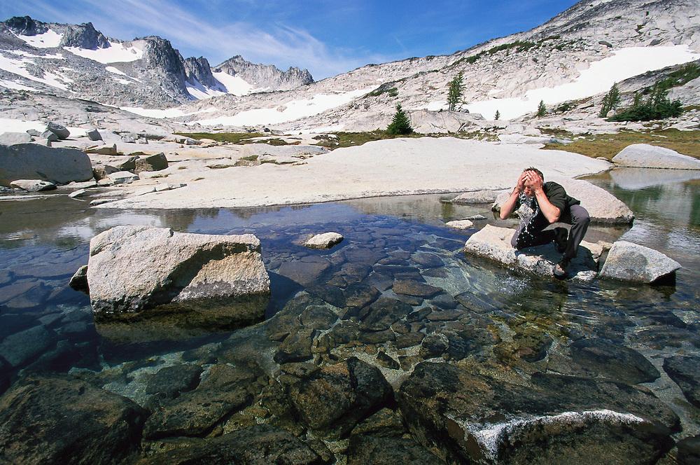 Young man enjoying mountain stream water&#xA;<br />