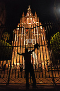 A man stands defiantly at the gates of San Miguel Archangel Arcángel church known locally as the Parroquia, as he taunts the guardians inside at the start of the La Alborada festival September 29, 2018 in San Miguel de Allende, Mexico. The festival celebrates the cities patron saint with a two hour-long firework battle at 4am representing the struggle between Saint Michael and Lucifer.