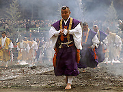 Yamabushi or Mountain priests in Yellow and purple robes walk across hot coals during the Hi Watari fire walking festival in Takao san Guchi near Tokyo Japan. Sunday March 11th 2007