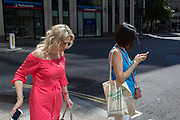 Two women hold mobile phones during the 2018 heatwave in the City of London, the capital's historic financial district, on 2nd August 2018, in London, England.