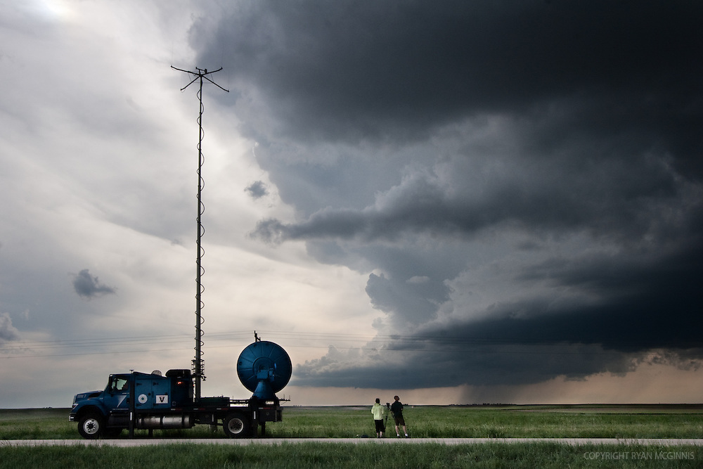 "Storm chasers with Project Vortex 2 watch a distant wall cloud and supercell in Goshen County, Wyoming, June 5, 2009. The truck at right is the ""Doppler on Wheels"" truck. Project Vortex 2 is a two year National Science Foundation and NOAA funded science mission to study tornadoes and supercell thunderstorms."