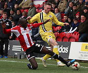 Toumani Diagouraga tackling Aiden O'Brien during the Sky Bet Championship match between Brentford and Millwall at Griffin Park, London, England on 21 March 2015. Photo by Matthew Redman.