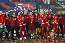 """LIVERPOOL, ENGLAND - Wednesday, July 22, 2020: Liverpool players sing """"You'll Never Walk Alone"""" after being crowned Premier League champions after the FA Premier League match between Liverpool FC and Chelsea FC at Anfield. The game was played behind closed doors due to the UK government's social distancing laws during the Coronavirus COVID-19 Pandemic. Liverpool won 5-3. Goalkeeping coach John Achterberg, physio Jose Luis Rodriguez Robledo, Sadio Mané, Roberto Firmino, goalkeeper Alisson Becker, head of nutrition Mona Nemmer, Fabio Henrique Tavares 'Fabinho', Divock Origi, Naby Keita. (Pic by David Rawcliffe/Propaganda)"""