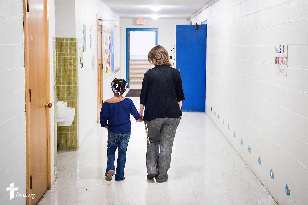 Principal Carrie Miller walks with a young student back to class through the lower hallway of Mount Calvary Lutheran School on Wednesday, May 28, 2014, in Milwaukee, Wis. LCMS Communications/Erik M. Lunsford