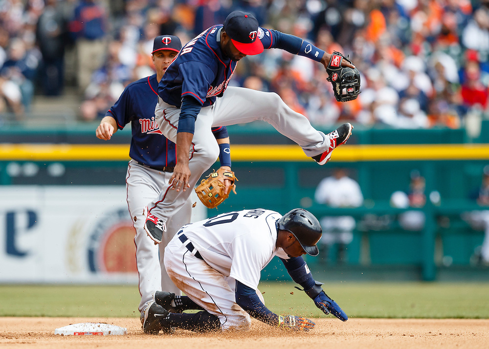 Apr 6, 2015; Detroit, MI, USA; Minnesota Twins center fielder Danny Santana (39) leaps over Detroit Tigers left fielder Rajai Davis (20) after he makes the throw to complete a double play as he slides into second base at Comerica Park. Mandatory Credit: Rick Osentoski-USA TODAY Sports