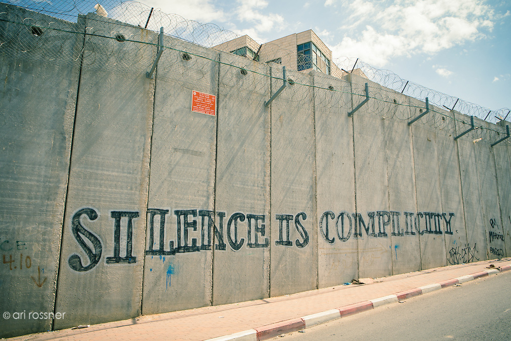 "The separation barrier between Israeli and Palestinian Territories from Israeli side.  A sign saying: ""mortal danger - military zone, any person who passes or damages the fence endangers his life"" and a graffiti saying ""silence is complicity"""