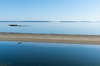 The sandbar at Cordova Bay rises at low tide on a sunny summer day in Victoria, BC, and is gloriously peaceful.